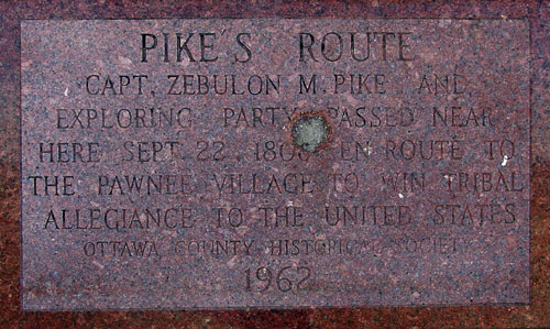 """Plaque reads: """"PIKE'S ROUTE CAPT. ZEBULON M. PIKE AND EXPLORING PARTY PASSED NEAR HERE SEPT. 22, 1806, EN ROUTE TO THE PAWNEE VILLAGE TO WIN TRIBAL ALLEGIANCE TO THE UNITED STATES. OTTAWA COUNTY HISTORICAL SOCIETY 1962"""""""